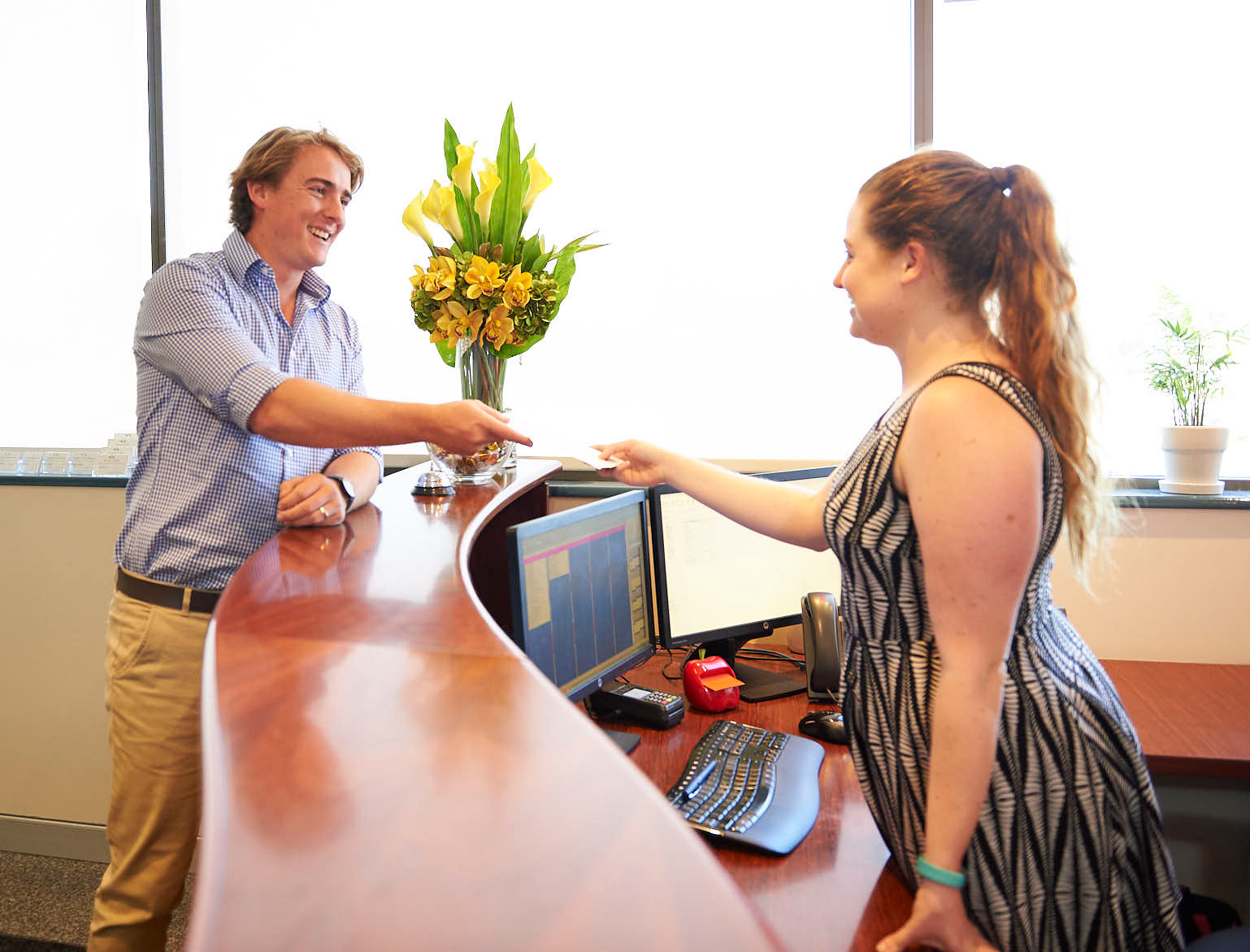 Man speaking with receptionist at Paragon Consultants office reception in Nedlands WA